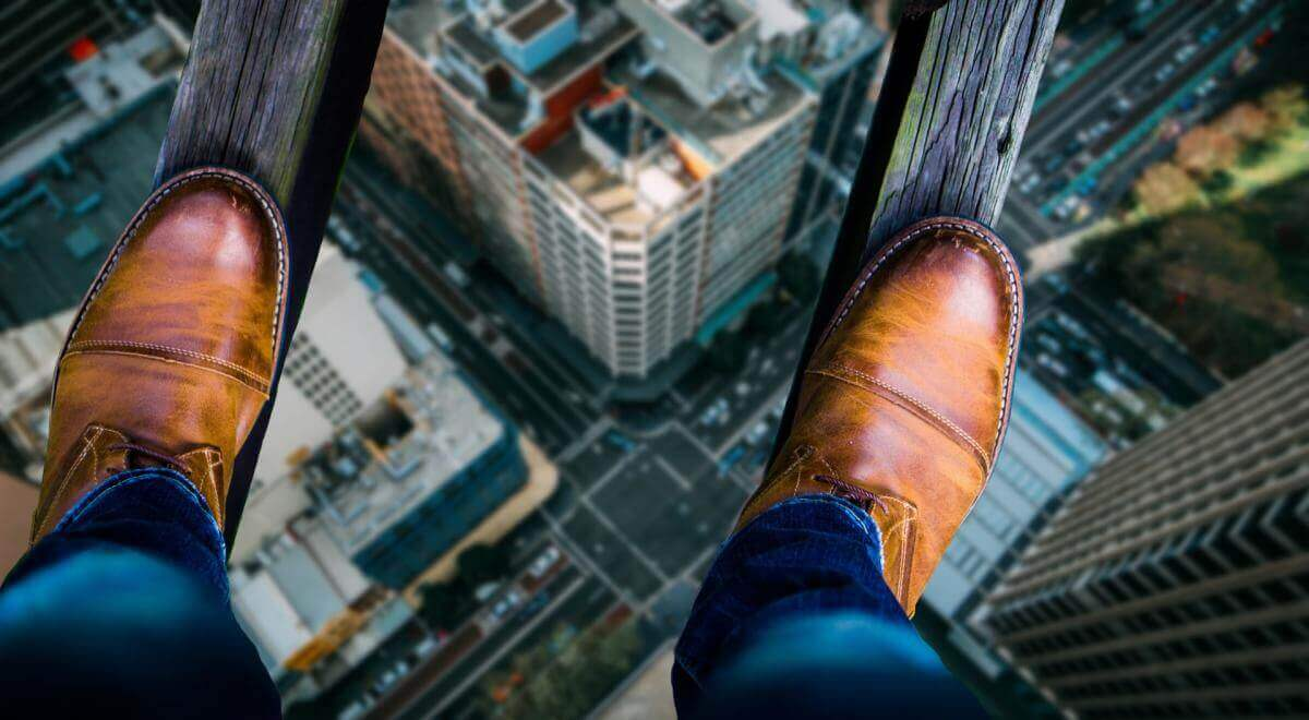 Symbolic image for fear of failure. Shows two narrow boards stretching high above a city. Viewpoint is from person balanced on those boards, looking down at their shoes, standing on the boards, with the cityscape far below.