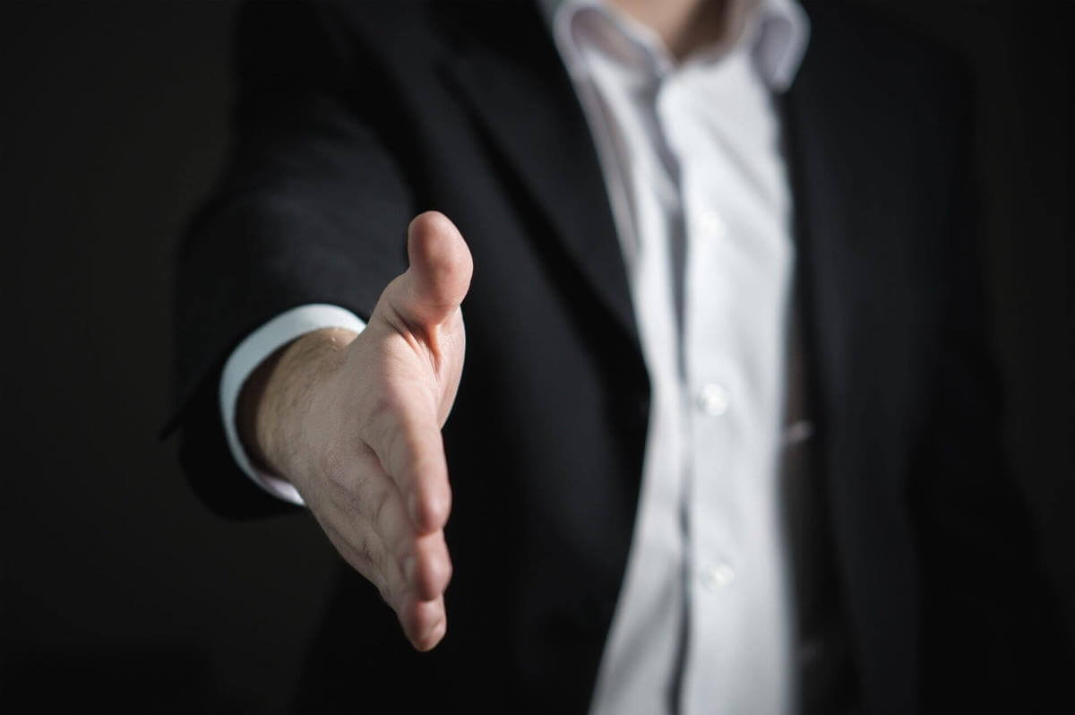 A picture of a man, visible from the neck to the waist. He's wearing a black suit jacket and white button-down shirt. His hand is extended toward the camera, reaching for a handshake. This is meant to symbolize keeping your focus on sales.