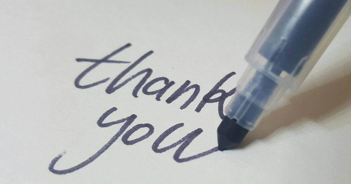 "Picture of the words ""thank you"" written by hand on a piece of paper. The pen is still visible in the picture and has just completed the ""u"" in the word ""you""."