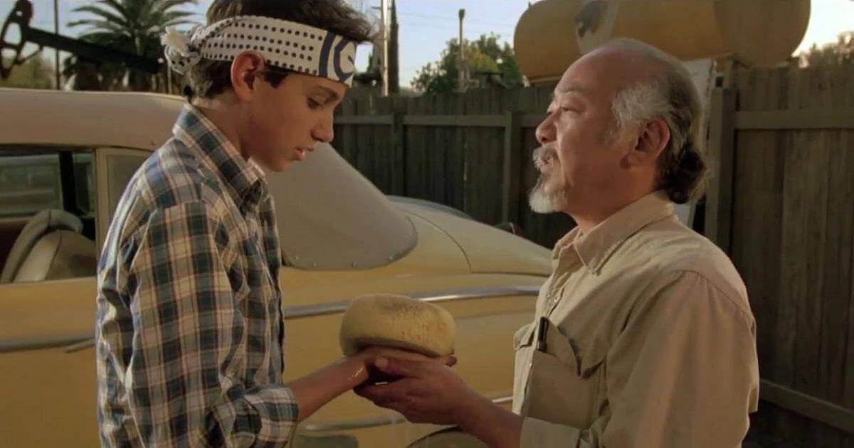 "Screen shot from Karate Kid of Daniel-son and Mr. Miyagi. Miyagi is handing Daniel-son the sponge with which to ""wax on, wax off"". Image is symbolic of self discipline."