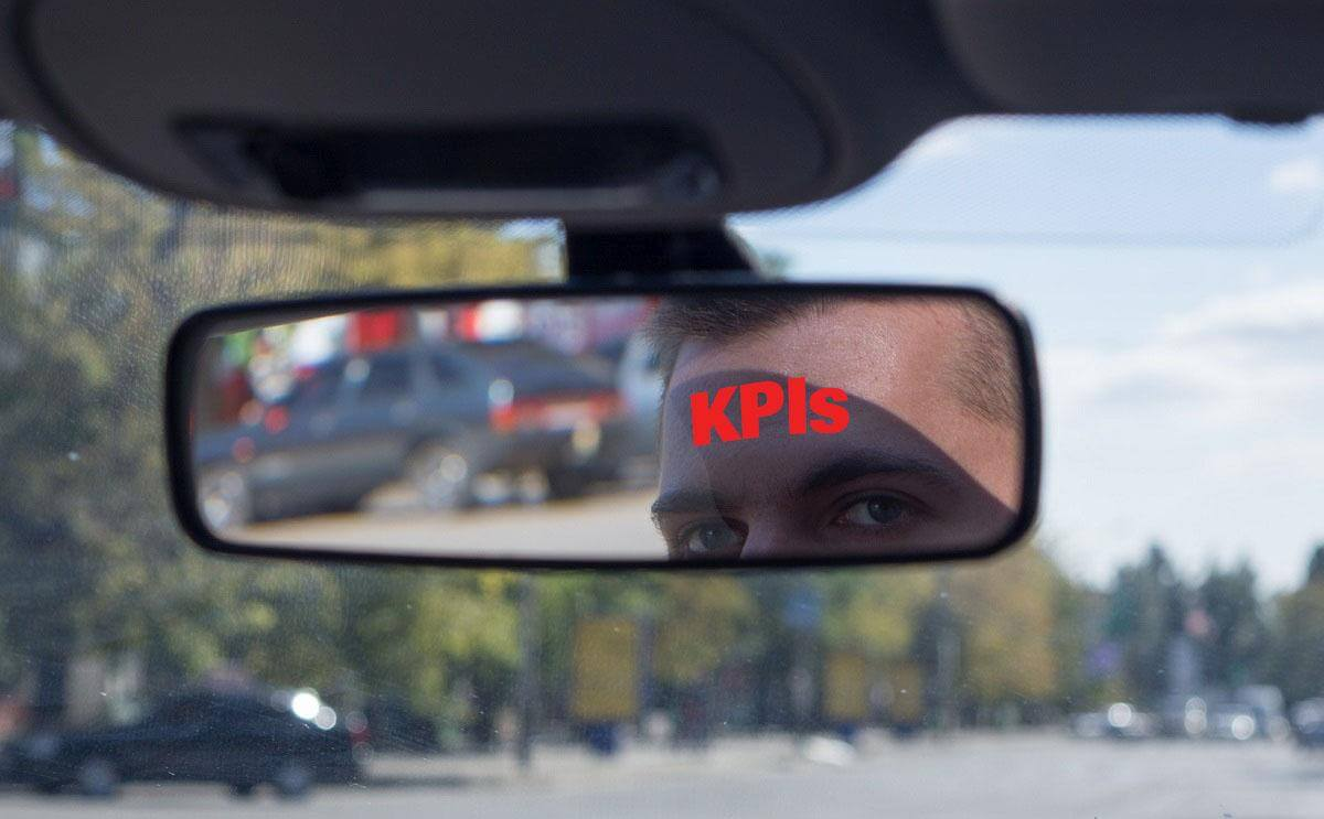 "A closeup of the reflection of a man's face in the review mirror of his car. Across his forehead is the work ""KPIs"" in red letters."