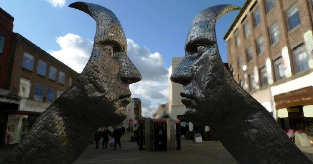 Leadership vs Management: A picture of sculpture of two metal faces, facing each other, two feet apart. From Medford, England. In this case, the faces are to represent Leadership and Management.