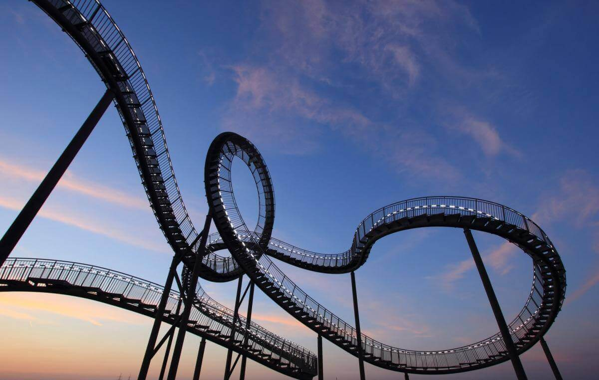 Large, winding roller coaster set against a beautiful blue afternoon sky.