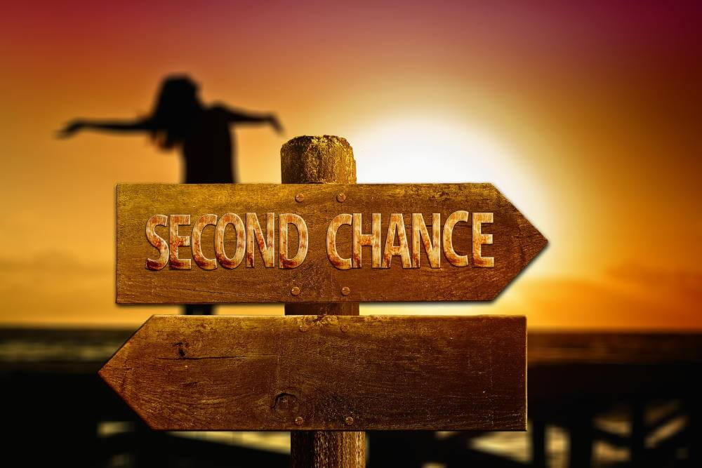 """In the background, a yellow sunset against an orange sky. A silhouette of a woman with her arms oustretched in the mid-ground. In the foreground, a wooden signpost that points in two directions. One arm reads """"Second chance"""". The other is blank."""