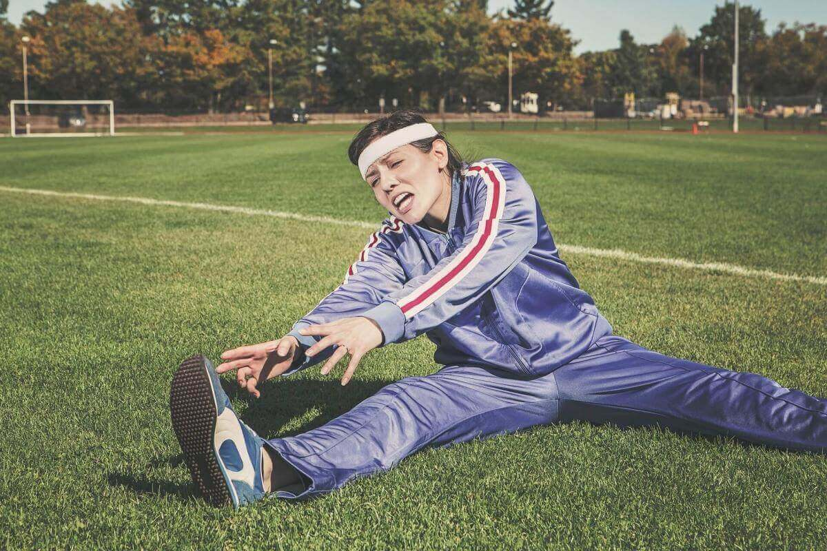 A picture of a woman wearing a blue track suit sitting on a sports field stretching her hamstrings. She looks frustrated and in pain.