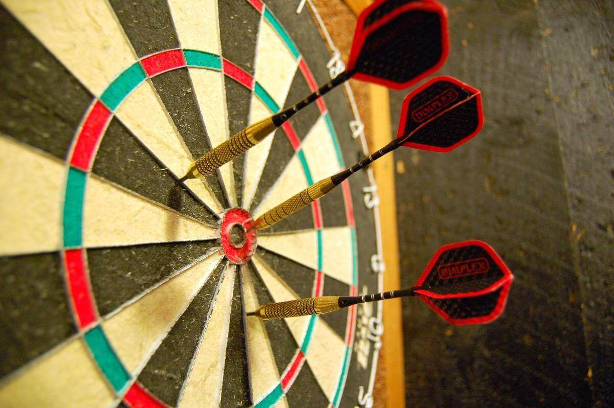 A picture of a dartboard with three darts sticking out of it. One is in the bullseye, the other two are a little bit outside the bullseye.