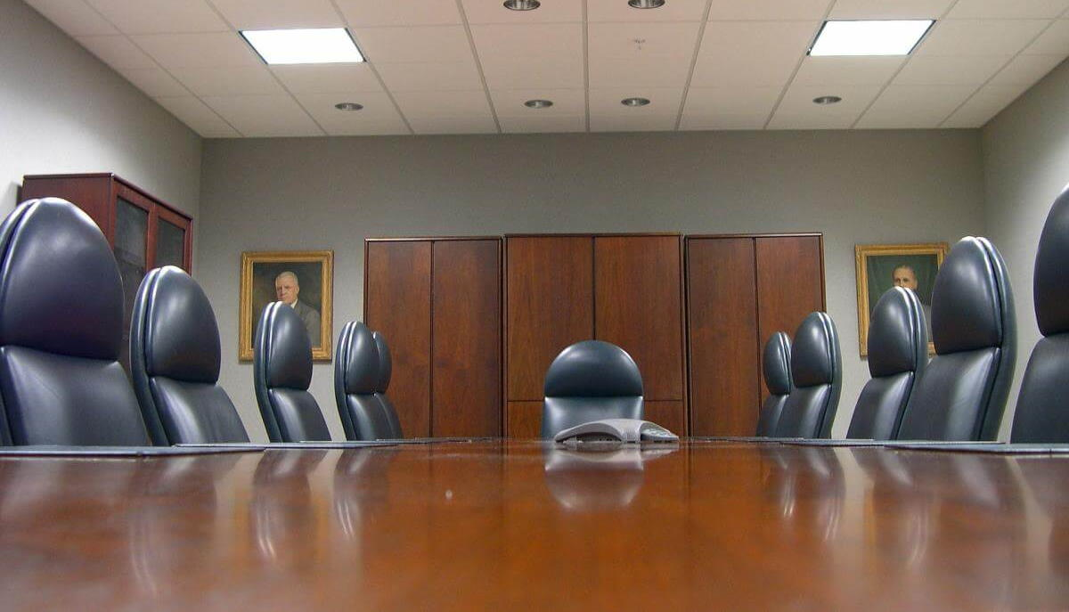 A picture of a typical VC backed company boardroom, complete with long table and a bunch of empty executive chairs.