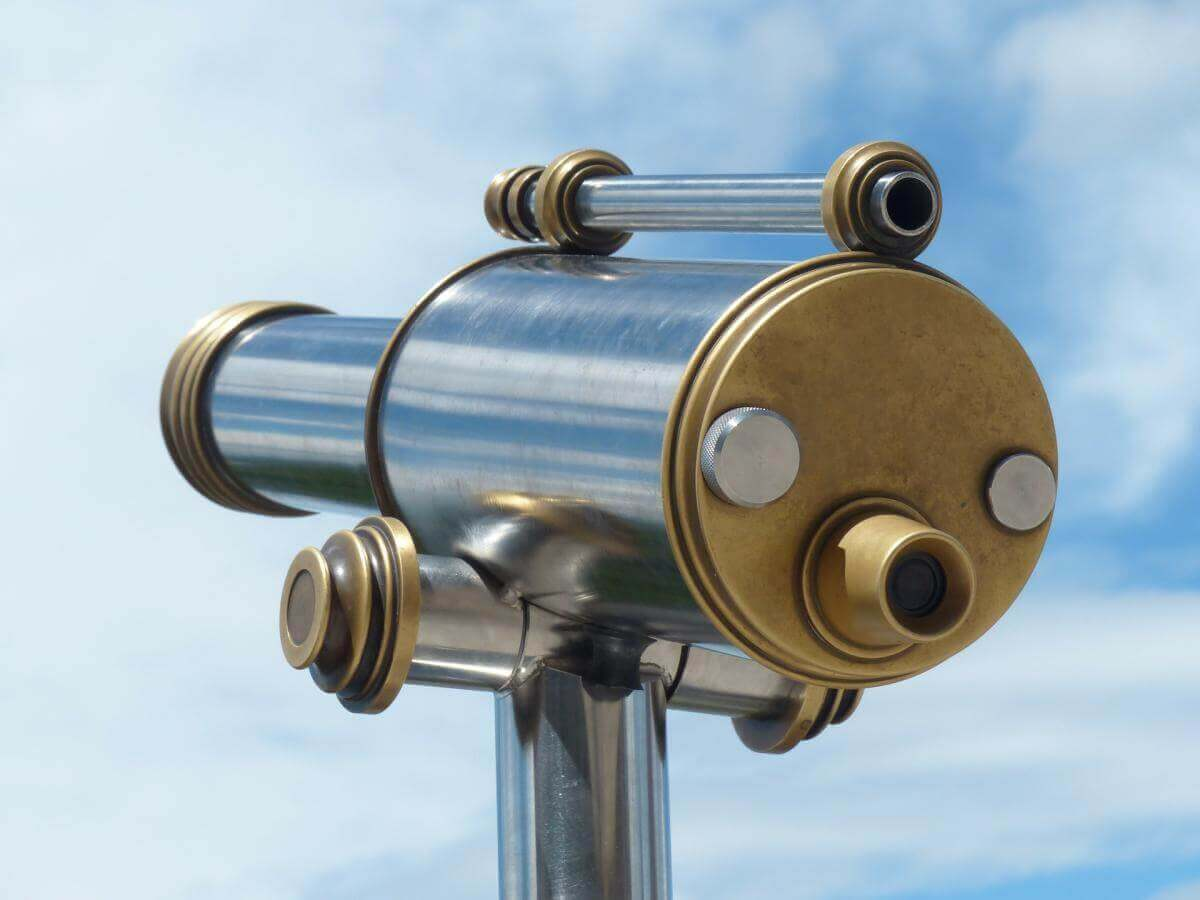 An image of a telescope aiming off into the great blue yonder. It's the type of telescope used on observation decks to look at the surroundings. In this case, the telescope is symbolic of vision.