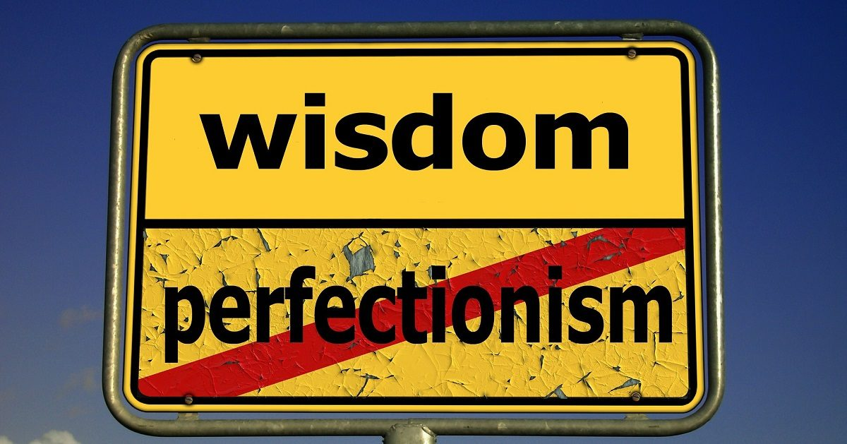 "A picture of a yellow sign with black letter. The top section of the sign says ""wisdom"". The bottom section of the sign says ""perfectionism"", with a red slash through it. The wisdom portion of the sign is in great shape with new paint. The perfectionism portion of the sign has peeling paint and looks bad."